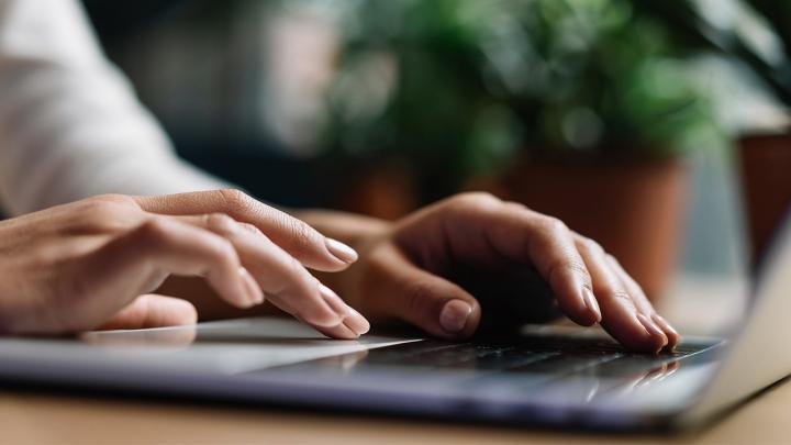 Dizüstü bilgisayarda yazı yazan kadının ellerine yakın çekim